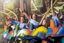 Enthusiastic Friends Cheering On Roller Coaster At Amusement Park