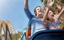 Enthusiastic Couple Cheering And Riding Amusement Park Ride