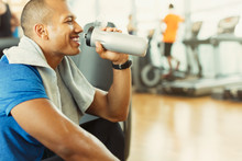 Smiling Man Drinking Water At Gym