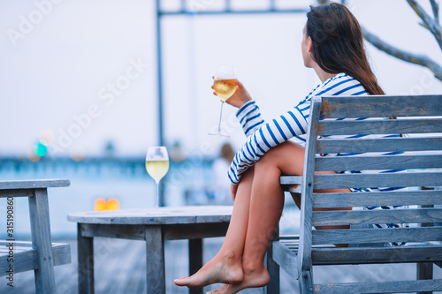 Fototapeta Young girl with white wine at evening outdoor cafe. obraz