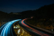 Leinwanddruck Bild - Light trails (long exposure) of cars driving an S-Shape curve on the German Autobahn at night