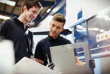 Workers Reviewing Paperwork In Steel Factory