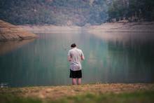 Rear View Of Man Fishing At La...