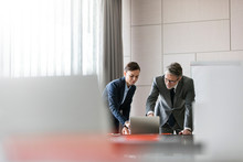 Businessman And Businesswoman Using Laptop In Conference Room