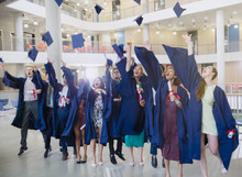 College Graduates In Cap And Gown Throwing Caps Overhead
