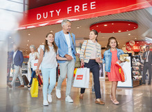 Family Leaving Airport Duty Free Shop With Shopping Bags