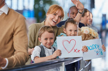 Mother And Children With Welcome Signs For Father At Airport