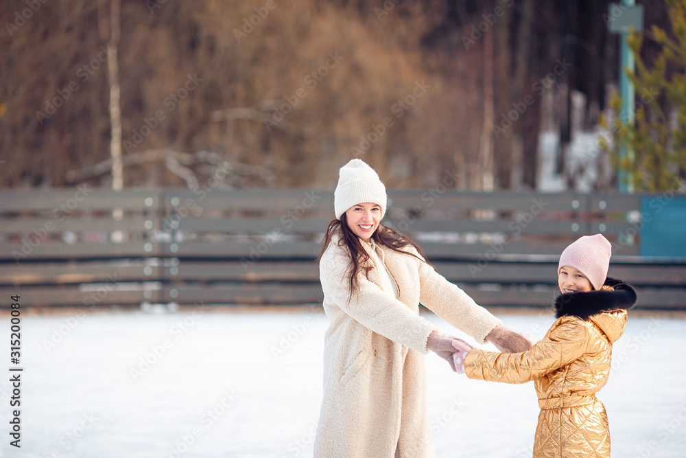 Fototapeta Little adorable girl with her mother skating on ice-rink