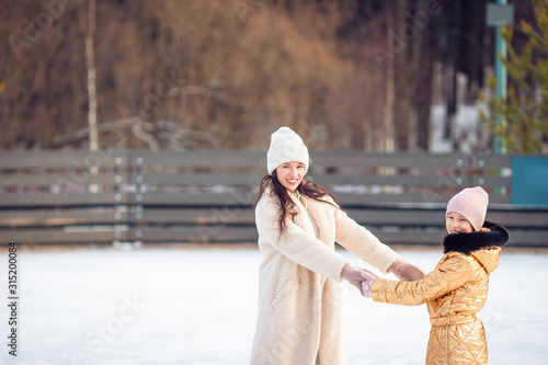 Fototapeta Little adorable girl with her mother skating on ice-rink obraz