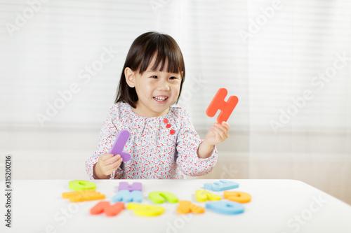 Photo toddler girl learning alphabet letter at home against white background