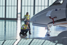 Air Traffic Control Ground Crew Workers Examining Corporate Jet In Airplane Hangar