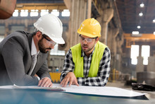 Manager And Engineer Reviewing Blueprints In Steel Factory