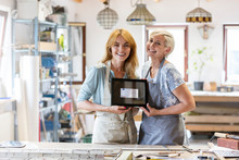 Portrait Smiling Small Business Artists Showing Framed Euro Banknote In Studio