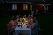 Family Enjoying Candlelight Dinner At Patio Table Outside House At Night