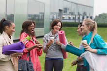 Women Friends With Yoga Mats And Coffee Talking Outside Gym