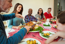 Family Enjoying Christmas Turkey Dinner At Table