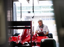 Manager With Clipboard Examining Formula One Race Car In Repair Garage