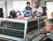 Formula One Racing Team Reviewing Diagnostics On Computers In Repair Garage