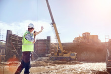 Construction Worker Foreman Using Walkie-talkie Directing Crane At Sunny Construction Site