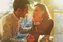Boyfriend Proposing To Surprised, Happy Girlfriend In Cafe