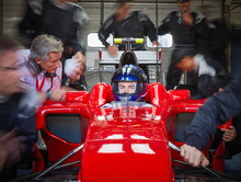 Pit Crew Working Around Serious Formula One Race Car Driver