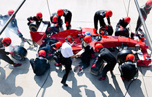 Manager Stopwatch Timing Pit Crew Replacing Tires On Formula One Race Car In Pit Lane