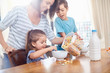 Mother pouring cereal for daughter at breakfast table