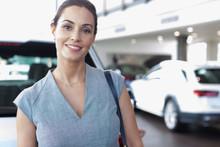 Portrait Confident Female Customer In Car Dealership Showroom
