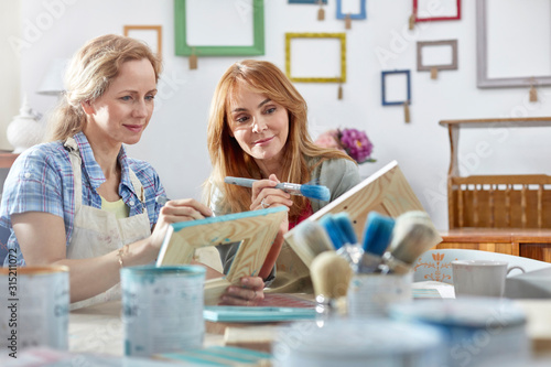 Female artists painting picture frames in art class workshop - 315211072
