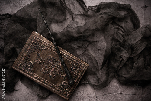 Canvas Print Old book with spells and magic wand on gray background with witch rag