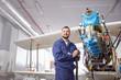 Portrait confident male airplane mechanic working on biplane in hangar