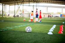 Football , Marker Cone And Ladder Drills On Green Artificial Turf With Blurry Kid Soccer Players Are Training Background. Soccer Academy.