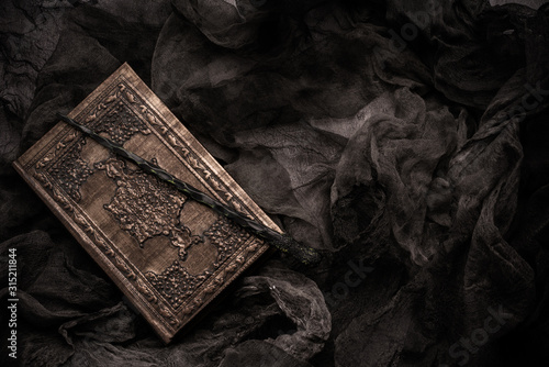 Cuadros en Lienzo Old book with spells and magic wand on gray background with witch rag