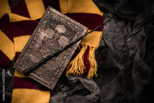 Subjects of the school of magic. Scarf, magic wand, book of spells on grey dark rag background.