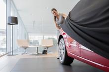 Car Saleswoman Removing Cover ...