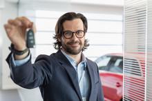 Portrait Confident Car Salesman Holding, Showing Car Key In Car Dealership Showroom
