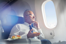 Senior Businessman Drinking Whiskey In First Class, Looking Out Airplane Window