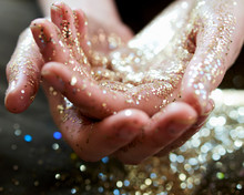 Close Up Hands Cupping Gold Glitter