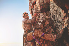 Focused Male Rock Climber Hanging From Rock