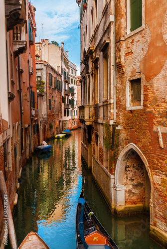Obraz View of a characteristic Venice narrow canal with gondola and old traditional houses in the Castello District - fototapety do salonu