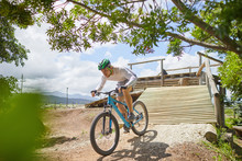 Focused Man Mountain Biking Down Sunny Obstacle Course Ramp