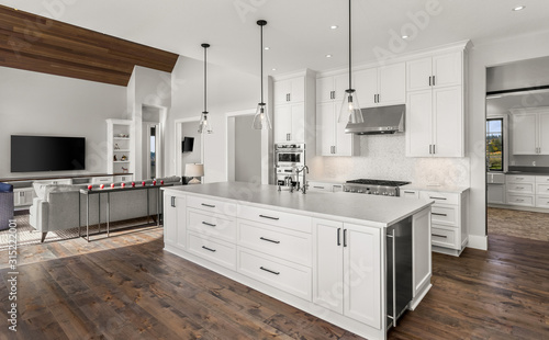 Beautiful kitchen in new luxury home with stainless steel appliances, pendant li Tableau sur Toile