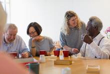 Volunteer Talking Senior Man Playing Games At Table In Community Center