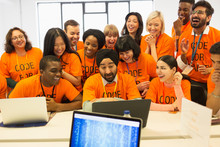 Happy Hackers Sharing Laptop, Coding For Charity At Hackathon