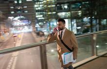 Businessman Talking On Smart Phone, Walking On Urban Pedestrian Bridge At Night
