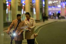 Business People Bicycle Paperwork Walking On Urban Street At Night