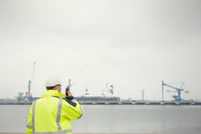 Dock Worker With Walkie-talkie At Commercial Dock