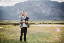 Portrait Father And Baby Son Standing In Rural Field