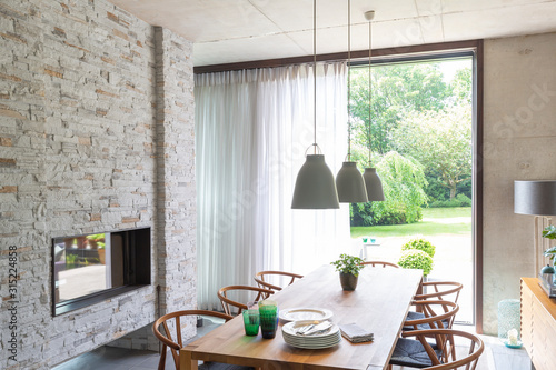 Pendant lights over dining table in modern dining room with brick fireplace - 315224858