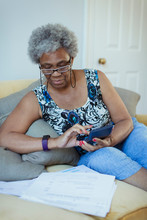 Senior Woman With Calculator Reviewing Bills